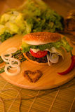 Homemade hamburger on the wooden desk. Homemade hamburger from white bread or bun with sesame with beef steak, slices tomatoes, raw onion rings, lettuce, Dijon Stock Photo