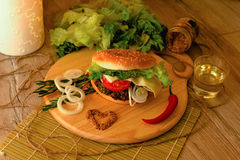 Homemade hamburger on the wooden desk. Homemade hamburger from white bread or bun with sesame with beef steak, slices tomatoes, raw onion rings, lettuce, Dijon Royalty Free Stock Images