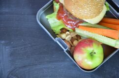 Homemade Hamburgers with lettuce in lunchbox. with orange juice. banana nuts. vegetables carrots and cucumber. On the