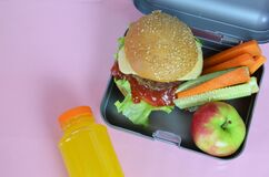 Homemade Hamburgers with lettuce in lunchbox on the table. with bright yellow orange juice. with banana nuts. Sliced