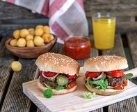 Homemade hamburgers with tomatoes, onions and pickles. Served with homemade tomato sauce stock image