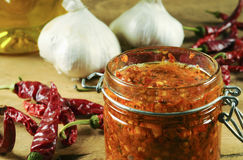 Homemade harissa sauce in a small jar stock photography