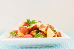 Healthful Potato Salad in a White Bowl. Homemade healthful potato salad made with new potatoes, turkey bacon, Italian parsley and smothered in a fresh homemade stock photo