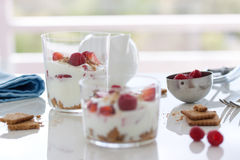 Homemade healthy dessert in a glass with yogurt, fresh fruits and cookies for breakfast Stock Images