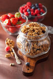 Homemade healthy granola in glass jar and berries Stock Photos