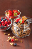 Homemade healthy granola in glass jar and berries Royalty Free Stock Images