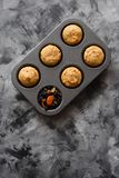 Homemade healthy imperfect sweets. Muffins with dried fruits in baking pan on dark background minimalist style top view. Copyspace royalty free stock photo