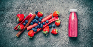 Homemade healthy refreshing fruit beverages in bottle with ingredients. Red berries and fruits smoothie, juicy vitamin drink on g. Ray concrete background , top stock photography