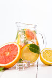 Homemade healthy water with grapefruit and ice in glass pitcher. Royalty Free Stock Image