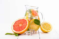 Homemade healthy water with grapefruit and ice in glass pitcher. Royalty Free Stock Images