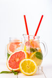 Homemade healthy water with grapefruit and ice in glass pitcher. Stock Photos