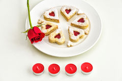 Homemade Heart shaped Almond Linzer cookies on white plate. Romantic set up red roses and candle lights ffor anniversary Stock Images