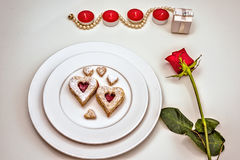 Homemade Heart shaped Almond Linzer cookies on white plate. Romantic set up red roses and candle lights ffor anniversary Royalty Free Stock Images
