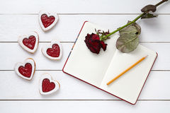 Homemade heart shaped cookies with empty notebook frame, pencil and red rose gift composition for Valentines Day Stock Photos
