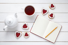 Homemade heart shaped cookies with empty notebook, pencil, cup of tea and teapot on white wooden background Stock Image