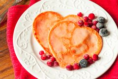 Homemade heart shaped pancakes with cranberries on porcelain plate. Closeup. royalty free stock photo