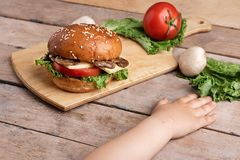 Girls hands near mushroom burger with cheese and tomatoes, raw champignons and lettuce, chopping board royalty free stock image
