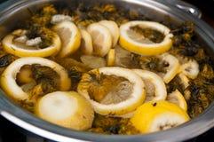Homemade herbal drink of dandelions and lemons. Making of a healthy herbal drink, homemade of lemon and dandelion flowers Royalty Free Stock Photo