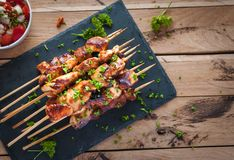 Homemade honey and beer BBQ chicken skewers with fresh parsley, top view royalty free stock photos