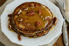 Homemade honey and pecan nuts pancakes on white plate and tablew Stock Photo