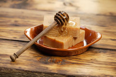 Homemade honey soap. With honey dipper on a plate stock photos