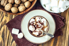 Homemade Hot Chocolate or Cocoa in White Mug with Marshmallows and walnuts on wooden background. Top view. Homemade Hot Chocolate or Cocoa in White Mug with Royalty Free Stock Images