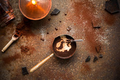 Homemade hot chocolate with milk, chocolate drops and cocoa powder on rustic background. Making chocolate. Royalty Free Stock Image