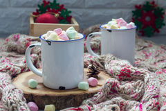 Homemade hot chocolate topped with marshmallow in enamel mug, warm scarf on background Stock Image