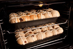 Homemade hot cross buns baking in oven. Trays of homemade fresh hot cross buns baking in oven Stock Photography