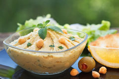 Homemade hummus with chickpeas. Olive oil and mint leaf in glass bowl. Closeup of chickpeas and sesame humus stock photo