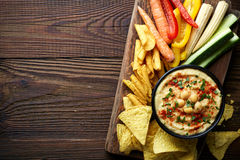 Homemade hummus, nachos and fresh vegetables. On wooden background from top view Stock Photos