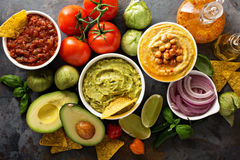 Homemade hummus, salsa and guacamole with corn chips. And vegetables overhead view Stock Images