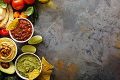 Homemade hummus, salsa and guacamole with corn chips. And vegetables overhead view Royalty Free Stock Photo