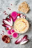 Hummus seasoned with olive oil and paprika and fresh vegetables: radishes, watermelon radish, red chicory, pomegranate. Homemade hummus seasoned with olive oil Royalty Free Stock Photography