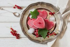 Homemade ice cream of red currant in shape of heart and on vintage dish and wooden background. Top view. Frozen drinks. Stock Photo