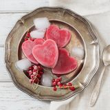 Homemade ice cream of red currant in shape of heart and on vintage dish and wooden background. Top view. Frozen drinks. Royalty Free Stock Photography