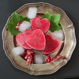 Homemade ice cream in shape of hearts. Red currant lemonade garnished mint and ice on vintage dish and black background. Top view. Frozen drinks Royalty Free Stock Images