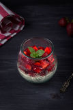 Homemade Italian dessert panna cotta with fresh strawberries and mint on a dark wooden background Stock Images