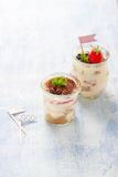 Homemade italian dessert tiramisu with strawberries, mint and cocoa in glass jars Royalty Free Stock Images