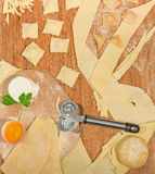 Homemade italian ravioli with fresh cheese,flour,egg,raw dough and aromatic herbs, placed on a rustic wooden table. Stock Photo