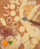 Homemade italian ravioli with prosciutto,flour,egg,raw dough and aromatic herbs, placed on a rustic wooden table. Stock Image