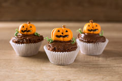 Homemade Jack O'lantern Pumpkin cupcakes. On wood background Stock Photos