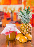 Homemade jam of pineapple with fresh fruit and little bread on a wooden table.  Stock Image