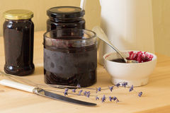 Homemade jam or preserves. Homemade jam, preserves, jelly with a jug, a knife, a spoon and a sprig of lavender Stock Photography