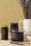 Homemade jam or preserves. Homemade jam, preserves, jelly with a jug of lavender, a knife and a spoon Stock Image