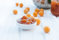 Homemade jam of yellow plum on a white board Royalty Free Stock Photos