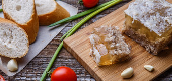 Homemade jelly meat with mustard, bread, tomatoes and garlic on the table. Holodets Stock Photos