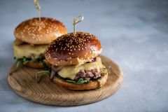 Homemade juicy burger with beef, cheese and caramelized onions. royalty free stock image