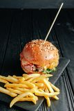 Homemade juicy burger on dark wooden board top view royalty free stock images