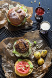 Homemade Juicy Pork Burger, a Veggie One with a Flag Topper and Buttered Baby Potatoes with Dill Stock Photo